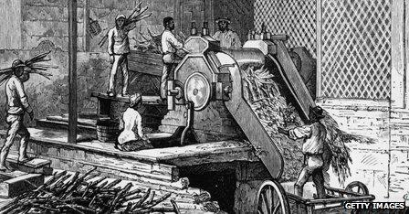 Workers operating a sugar cane crushing machine on a plantation in Jamaica, 1884