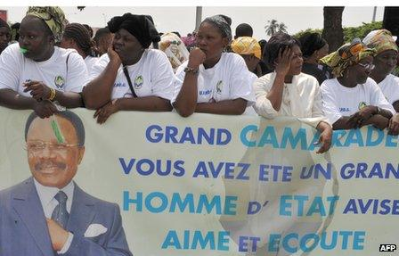 Women hold poster depicting the late President Omar Bongo at Libreville airport on 11 June 2009
