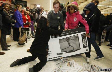 Shoppers wrestle over a television at an Asda superstore in Wembley, north London