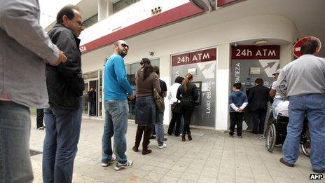 Cypriots and foreigners wait in line to withdraw money from an ATM of a Laiki (Popular) Bank branch in the old city of the capital, Nicosia, on 21 March 2013.