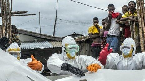 Workers in protective suits discard of body bag