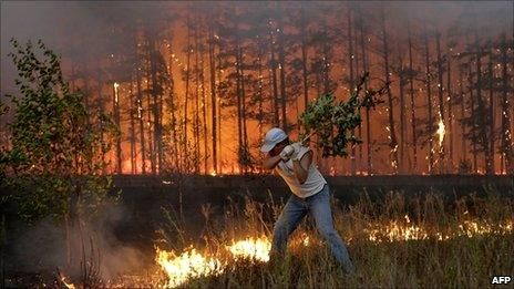 A man tries to stop fire near village of Dolginino in Ryazan region, about 100 miles southeast of Moscow, Russia, 4 August 2010