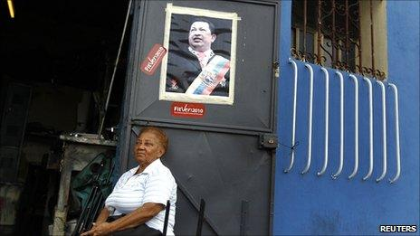 A woman sits outside a shop with a picture of Venezuelan President Hugo Chavez on the door in Caracas on 17 September 2010