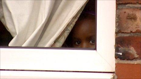 One of Flora's children, looking out a window at home