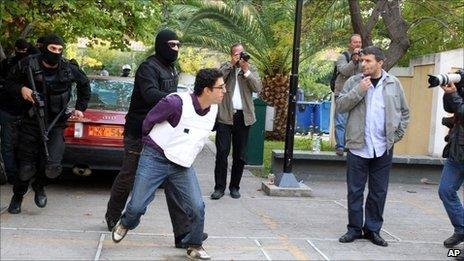 Greek police escort Panayotis Argyrou to a public prosecutor's office in Athens, 2 November