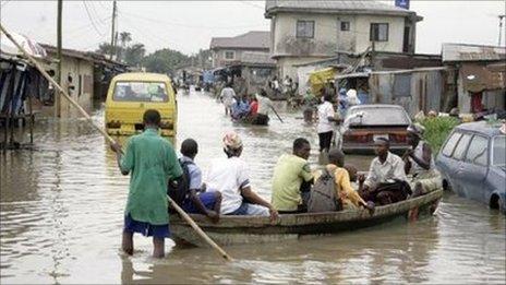 People in a canoe on a street in Cotonou