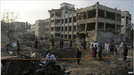 Pakistani investigators inspect the site of a bomb blast in Karachi a day after the attack (12 November 2010)