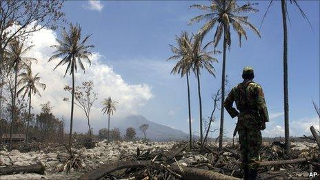 A soldier looks at Mount Merapi from an ash-covered field on 15 November 2010