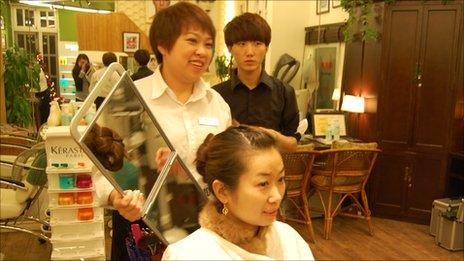 Cai Huilin holds up a mirror to a customer's head in Beijing