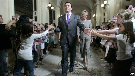 Arnold Schwarzenegger slapping the hands of school children