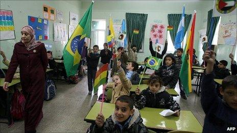 Children wave flags of Latin American countries.