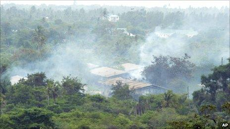 Smoke drifts over the Gongola Mboto military camp on the outskirts of Dar es Salaam Thursday Feb. 17, 2011