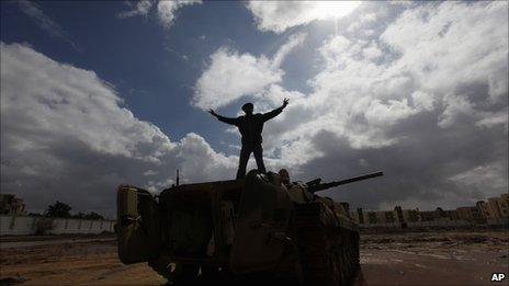 A Libyan man stands over a destroyed tank flashing a V signal, Al-Katiba military base, Benghazi, 24 February 2011