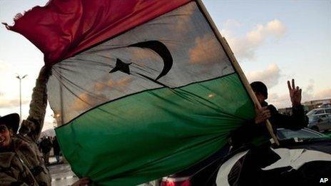 Libyan men hold the former royal flag as they drive past a demonstration against Libyan leader Muammar Gaddafi in Benghazi, eastern Libya, 27 February 2011