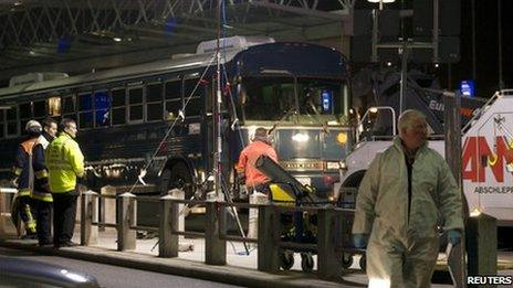 Investigators work around the bus attacked at Frankfurt Airport, 2 March