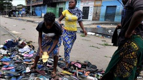 Women gather rubber sandals abandoned by women protesters shot on by troops in the Abobo neighbourhood of Abidjan, 3 March 2011.