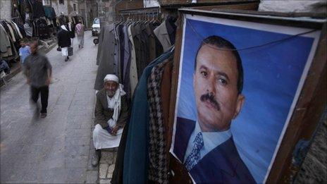 A shopkeeper in Sana'a waits for customers next to a poster of President Saleh. Photo: March 2011