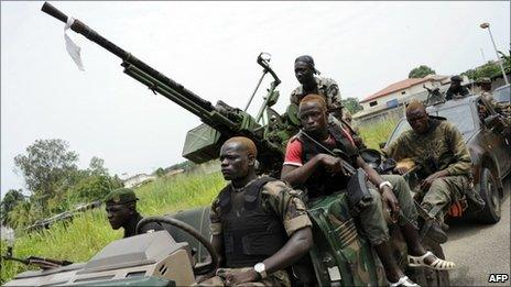 Pro-Ouattara armed militiamen patrol in a district of Abidjan on 13 April 2011.