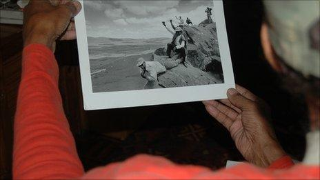 A former freedom fighter looks at a photo of his friends and colleagues