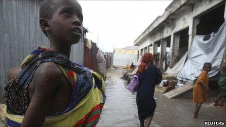 A Somali child carries her sibling as they wade through a flooded camp in Mogadishu, 14 July 2011