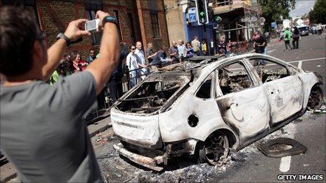 Man taking digital photo of burned out car
