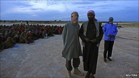 "Al Shabaab""s spokesman Sheikh Ali Mohamud Rage (R) and a foreign al-Qaeda official Abu Abdalla al Muhaajir (L) watch as food rations from al-Qaeda are distributed at the Ala-yasir Internally Displaced People (IDP) camp for al-Shabab militias, in Lower Shabelle, 50 km (31 miles) south of Somalia""s capital Mogadishu, October 13, 2011."