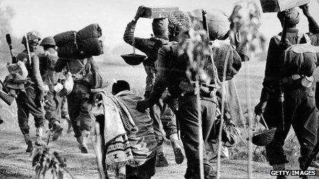 An elderly refugee walks alongside Indian troops advancing into the East Pakistan (Bangladesh) area during the Indo-Pakistani war of 1971