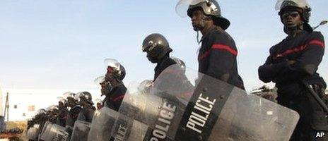 """Riot police stand guard over Place de l""""Obelisque in Dakar, Senegal, where hundreds of people gathered to protest the decision by the country's highest court to allow President Abdoulaye Wade to run for a third term in February's election"""