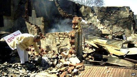 A businessman sorts through the remains of his burned shop in Ahmedabad, India - 4 March 2002