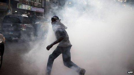 """An anti-government protestor flees from tear gas at a protest in Senegal""""s capital Dakar, February 21, 2012"""