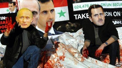 Avaaz activists wearing masks of Russian PM Vladimir Putin and Syrian President Bashar al-Assad dump bloodied body bags outside the UN's headquarters in New York (24 January 2012)