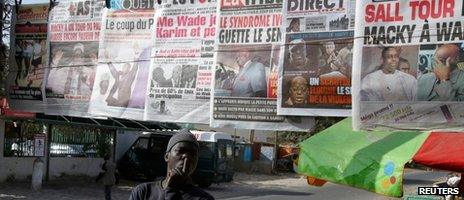 A man reads newspapers after the first results from Senegal's controversial presidential election indicate a tight race between incumbent Abdoulaye Wade and former Prime Minister Macky Sall at a newsstand in central Dakar on 27 February 2012