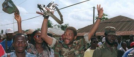 Charles Taylor (C) jubilates on 21 July 1990 with his rebel troops in Roberts Field after taking over the position from Liberian government troops
