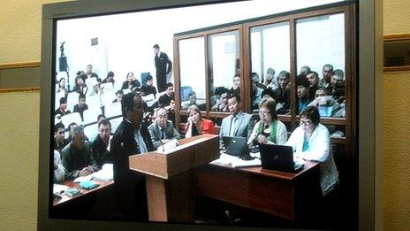 Witness testifying at the trial in Aktau as seen from a television screen