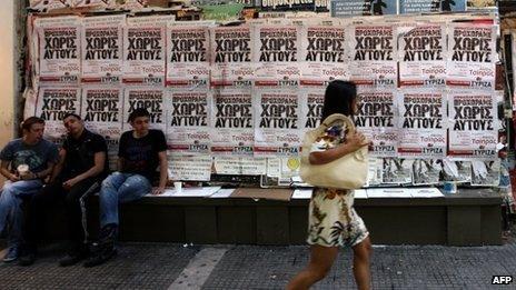 Woman walking past Syriza posters