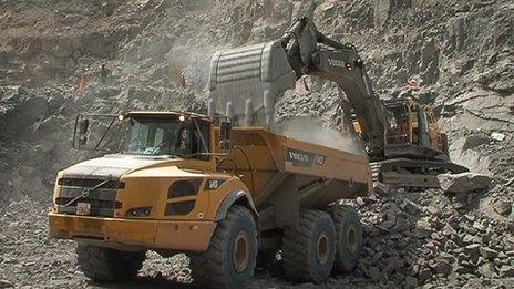 Digger and truck moving rocks