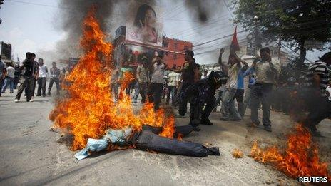 A Nepalese riot police officer drags away the burning effigy of Nepalese Prime Minister Baburam Bhattarai after it was set on fire by students affiliated to the Nepal Student Union, a student wing of the Nepali Congress Party, during a protest demanding the immediate resignation of the Prime minister in Kathmandu May 28, 2012.