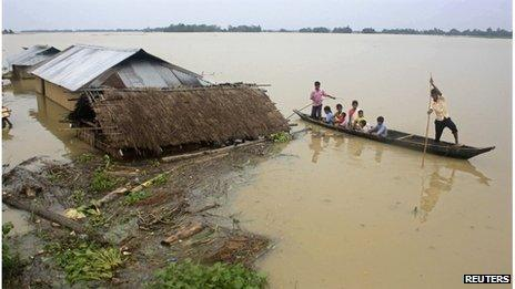 Flood-affected local residents move to safer places on a boat next to their damaged huts after heavy rains at Jajimukh village in the northeastern Indian state of Assam June 27, 2012