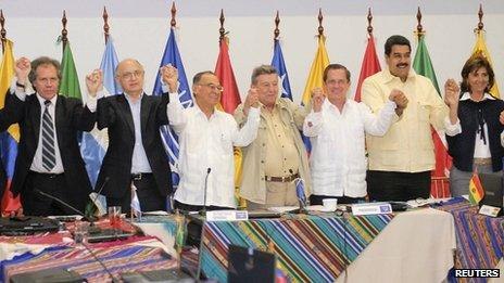Unasur foreign ministers join hands after issuing the declaration in Guayaquil