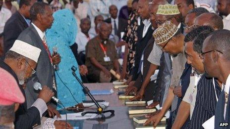 Members of Somalia's new parliament place their hands on the Koran as they are sworn in at Mogadishu's international airport