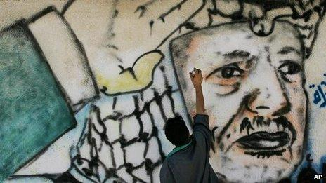 A Palestinian artist finishes a mural of Yasser Arafat near his head quarters in Gaza City