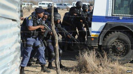 Police officers look at protesting Lonmin miners