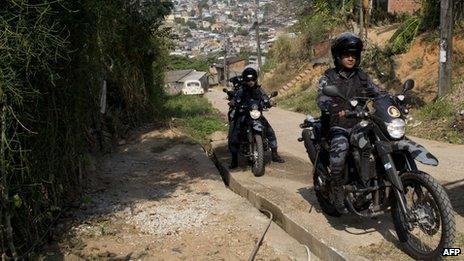 Police on motorbikes patrol the Chatuba favela