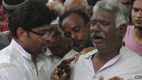 Relatives mourn the death of loved ones during a funeral for garment factory victims in Karachi on 13 September 2012.