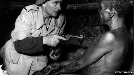 Mau Mau prisoner under guard in Kenya after a night raid organised by the British Army and the Kenya police to find members of the movement - November 1952