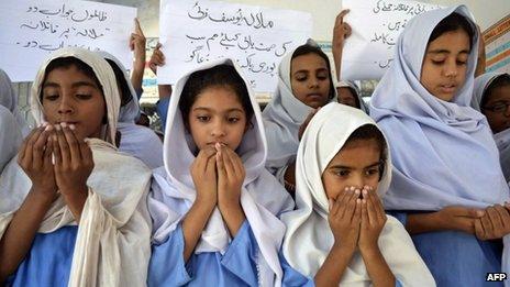 Pakistani schoolgirls in headscarves pray