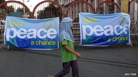A Muslim girl walking past a banner showing support for the signing of the peace deal between the government and MILF rebels in Manila, 14 October 2012