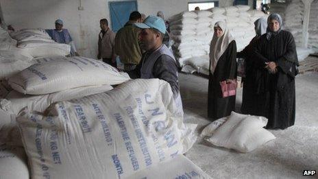 Women wait for flour rations from Unrwa at a refugee camp in Gaza City