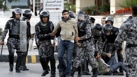 Jordanian policemen detain protesters blocking a main road during a demonstration against a rise in fuel prices in downtown Amman on 14 November