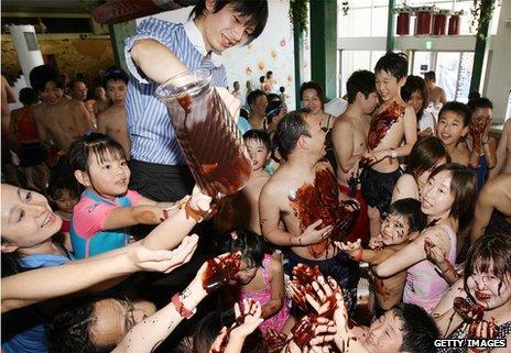 Visitors enjoy the chocolate-spa pool at the Hakone Kowakien Yunessun hot springs resort, Japan